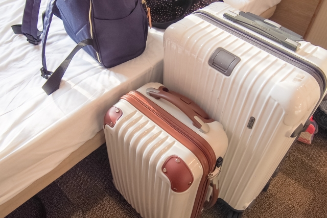 すっきりとした詰め方で荷物を詰めたスーツケースをホテルの部屋に置いている画像