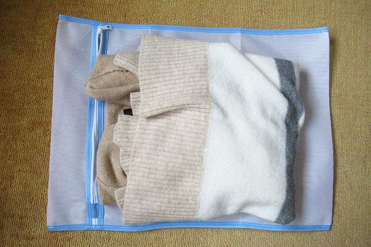 キャリーバッグの詰め方のコツ セーターを洗濯バッグに入れる画像