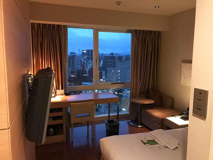 福岡天神ホテルユニゾに泊まってみた!【タリーズ直結でベンリ&見晴らしいい】夕暮れの福岡の街をのぞむ写真